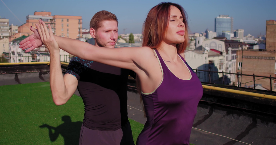 Couple is playing sports on the roof of the building. Guy's stretching the woman. View from the roof in the background. High quality 4k footage. 18 of October 2017. Kyiv, Ukraine.   Shutterstock HD Video #1059220367
