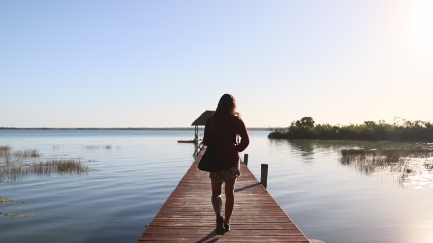 View of a Woman Walking on the Dock on Lake Bacalar with a Beautiful Blue Sky | Shutterstock HD Video #1059222062