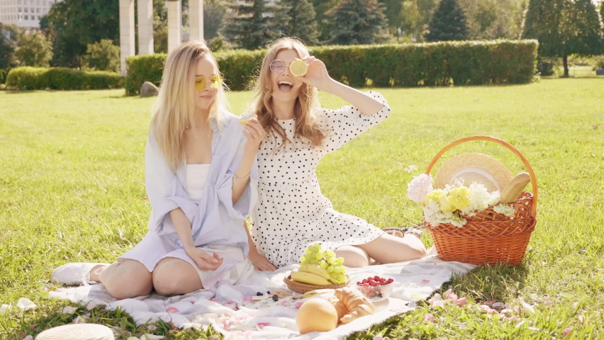 Two young beautiful hipster woman in trendy summer sundress and hats. Carefree women making picnic outside. Positive models sitting on plaid on grass, eating fruits and cheese.Holding sliced lemon Royalty-Free Stock Footage #1059223586