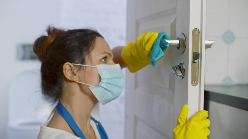 Woman housekeeper in mask wiping door knob with rag. Close up of maid in protective mask and rubber gloves disinfecting door doing house cleaning. Home cleaning service concept