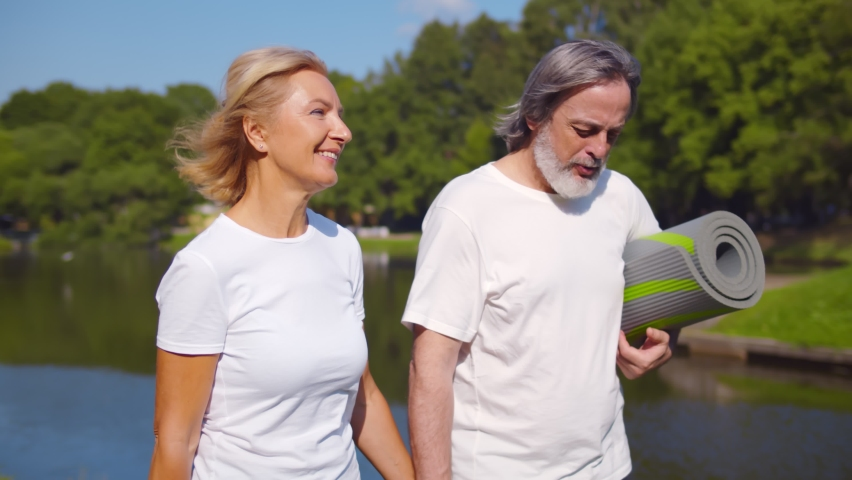 Lovely senior man and old woman holding yoga mat for exercising outdoor walking in park. Active healthy retired couple chatting and strolling by riverside after workout in summer park Royalty-Free Stock Footage #1059224942