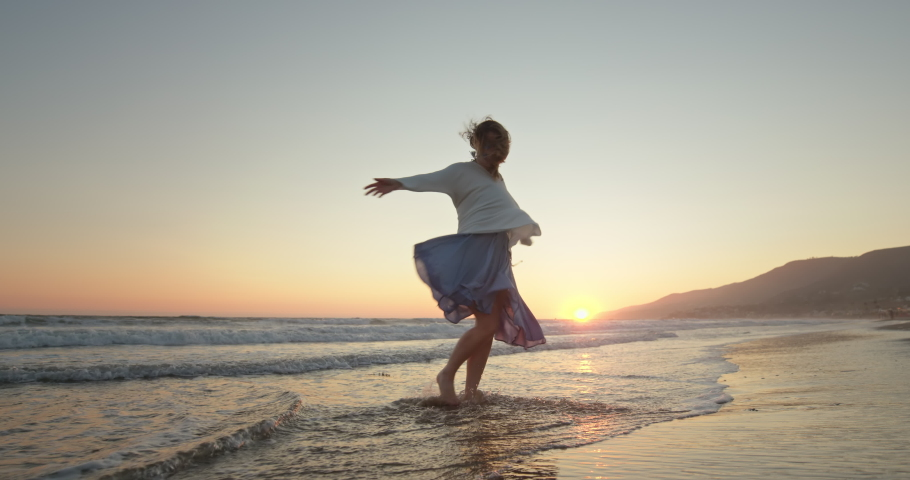 Woman on the beach. Beautiful girl enjoying the best of her life time and cinematic nature at sunset light. Happy model dancing and having fun on the ocean shore with wind blowing her hair and dress Royalty-Free Stock Footage #1059225788