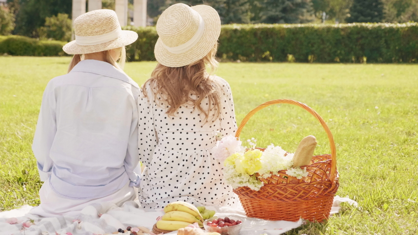 Back view.Two young beautiful hipster woman in trendy summer sundress and hats. Carefree women making picnic outside. Positive models sitting on plaid on grass, hugging and enjoying weekend  Royalty-Free Stock Footage #1059226562