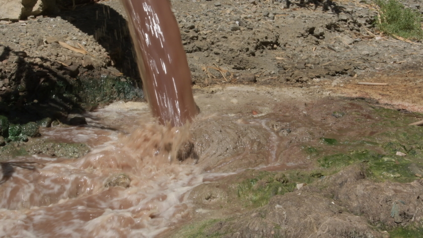 Torrent of sewage falling in a mountain of shit in the mouth of a river   Shutterstock HD Video #1059228980