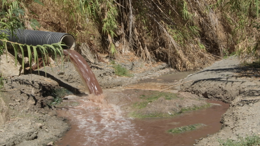 Sewage collector emanating sewage shit at the mouth of a river a sunny day   Shutterstock HD Video #1059228983