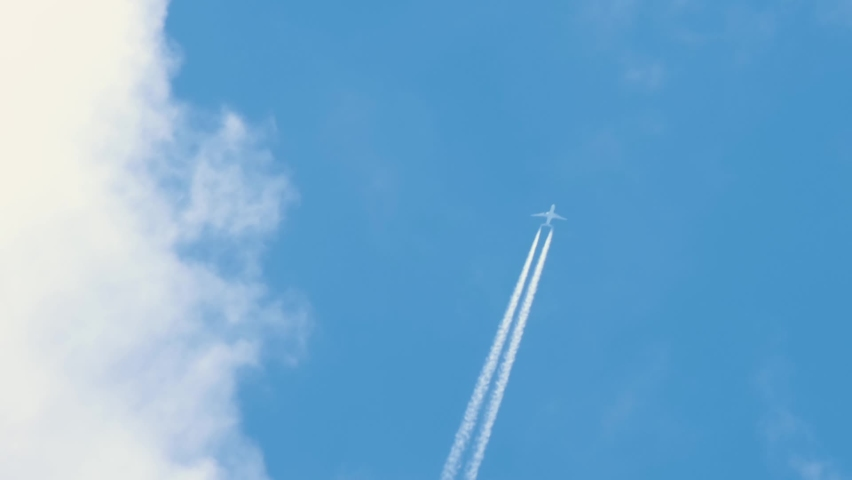 Passenger airplane at cruising altitude with contrail against blue sky. | Shutterstock HD Video #1059231614
