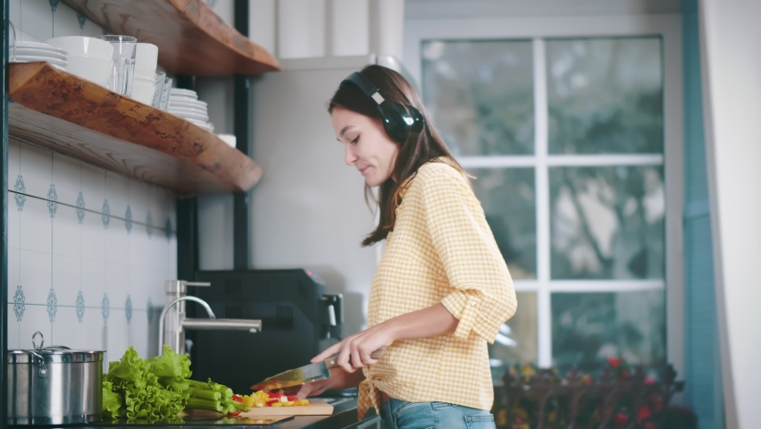 Emotional woman dancing in kitchen at home listening to music with headphones and cooking. Side view of pretty housewife cutting vegetables for lunch enjoying music in earphones