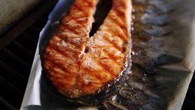 Delicious salmon fish steak cooked on grill for dinner in sea food restaurant.Tasty natural red fish fillet being cooked in kitchen on hot grill surface in close up video clip.Healthy natural seafood