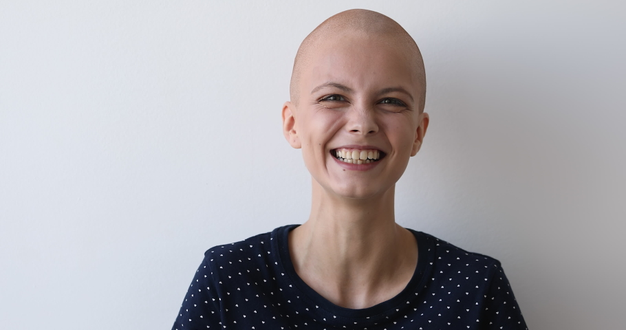 Bald hilarious young woman breast cancer patient posing on grey wall background laughs feels carefree believes in recovery celebrates remission, overcome oncology disease head shot studio portrait   Shutterstock HD Video #1059236186