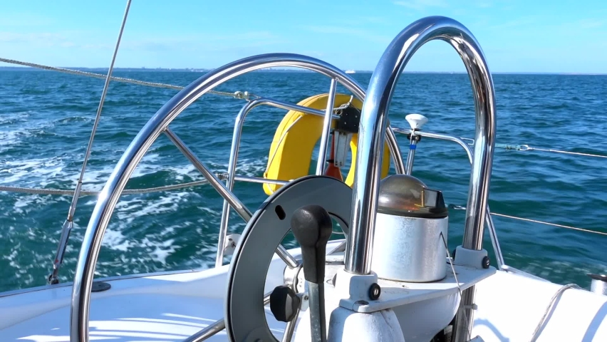 A sailing yacht boat in calm coastal waters with a nice breeze on a sunny day. Autopilot turning the wheel and helming steering the boat automatically on a set compass course.  | Shutterstock HD Video #1059236918