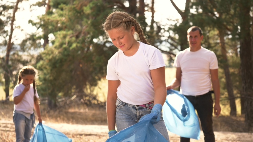 Happy family collects plastic trash in the park. Teamwork of volunteers to clean up plastic bottles, garbage. The child helps to work in a team. A group of people and children are working in the park   Shutterstock HD Video #1059237854