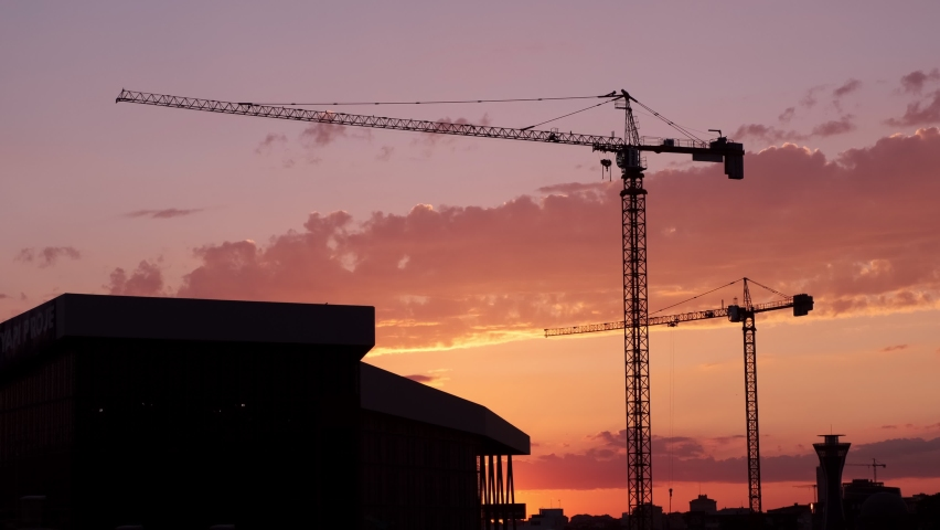 Silhouettes of construction tower cranes with buildings in pink and orange sunset. | Shutterstock HD Video #1059239843