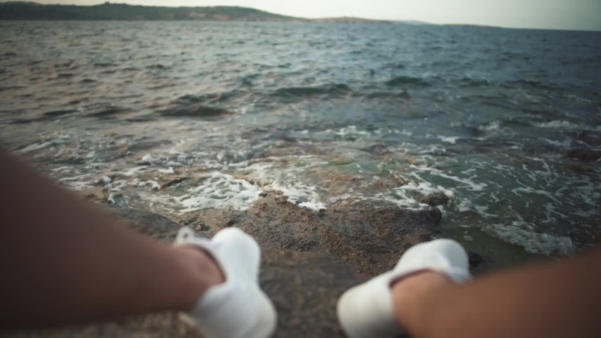 Legs in white sneakers on a rocky beach on the background of sea waves first person shooting focus moves to the sneakers | Shutterstock HD Video #1059240530