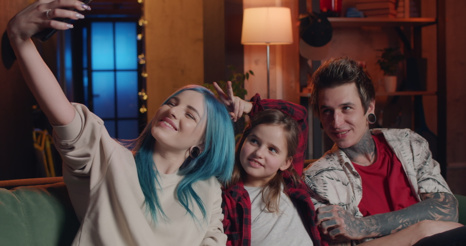 Portrait of happy family having fun while doing selfies at home. Young woman and man and their daughter posing for photo while sitting on sofa. Modern people with piercing and tattoos | Shutterstock HD Video #1059241217