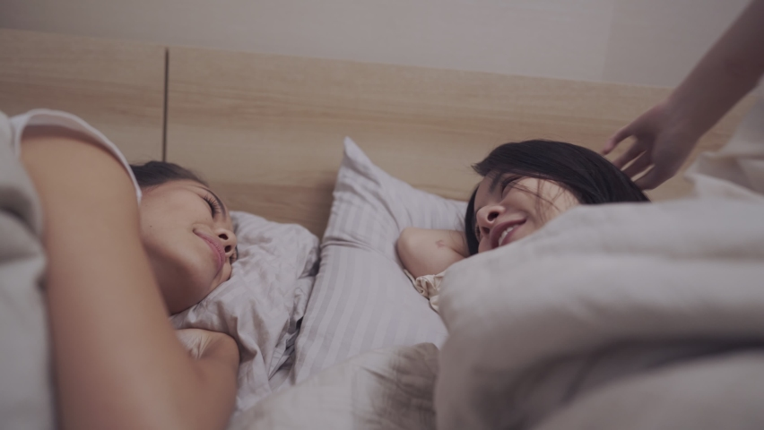 Asian lgbt lesbian couple cuddle inside warm blanket on the bed, looking and playing at each other  LGBT freedom, bonding relationship, sexual equality sharing love, transgender movement roommates | Shutterstock HD Video #1059242615