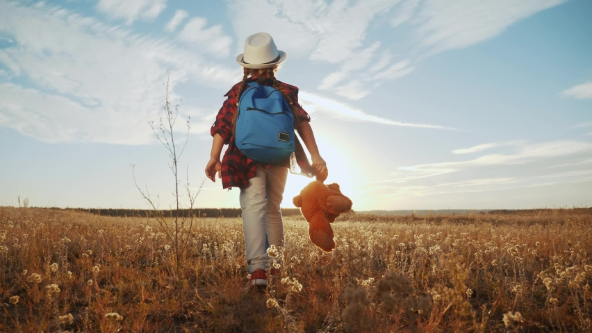 Little girl child walk in the park a toy teddy bear. kid dream happy family concept. daughter kid walk back outdoors. child walk with his back dream family. people in lifestyle the park | Shutterstock HD Video #1059242771