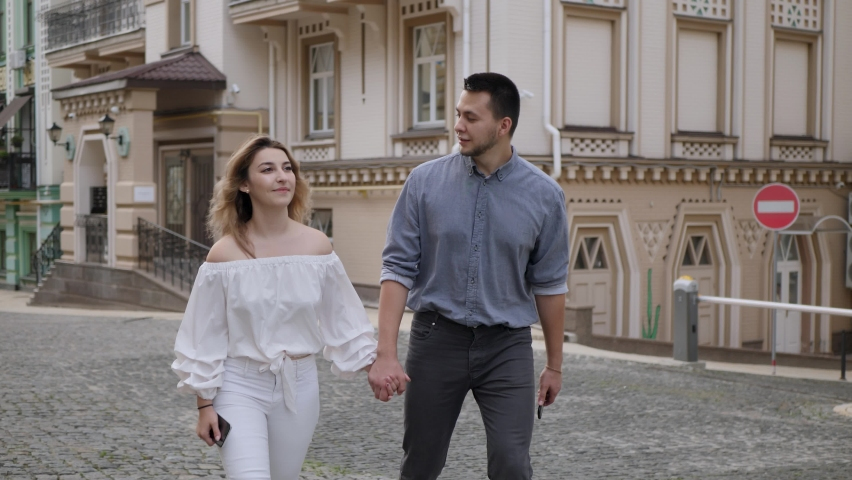 Stylish happy guy and girl in casual clothes are walking and holding hands along the street of the old city | Shutterstock HD Video #1059242987