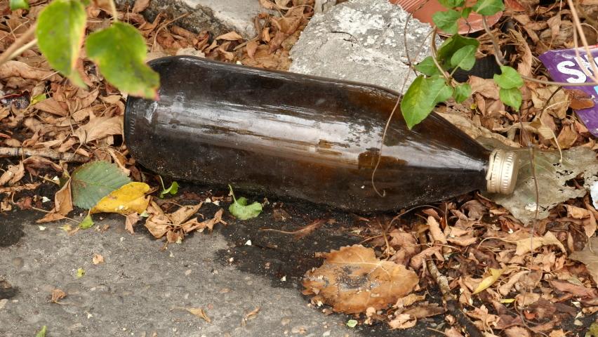 Pollution: glass bottle of beer thrown in a street in Getafe, Madrid, Spain. September 19, 2020.   Shutterstock HD Video #1059246593
