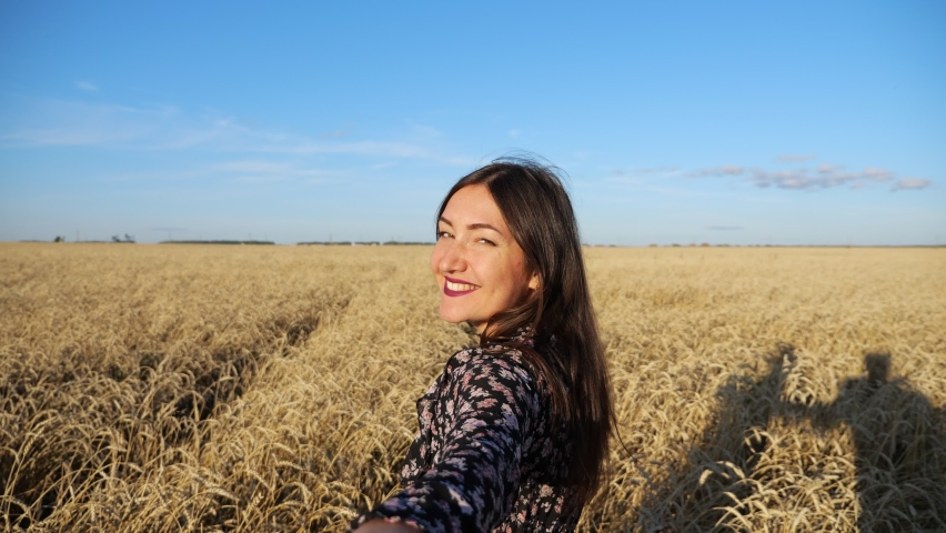 Brunette woman leads across a field of ripe wheat turning smiling. follow me concept | Shutterstock HD Video #1059246986