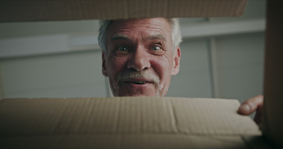 Joyful surprised gray-haired senior man pensioner opening cardboard box with surprise gift present on birthday special occasion, looking happy pleased and amazed. Royalty-Free Stock Footage #1059247121