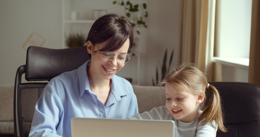 Babysitter woman does homework with little lady at laptop, sister helps preschool girl to draw, mother spends time with daughter at computer, teaches child at home, quarantine time electronic learning | Shutterstock HD Video #1059248483