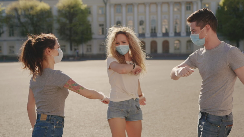 Social distancing. Multiracial Friends in protective face mask greet their elbows. Elbow bump is new greeting to avoid spread of coronavirus or covid-19 - Avoid or Stop handshakes due to pandemic | Shutterstock HD Video #1059248756