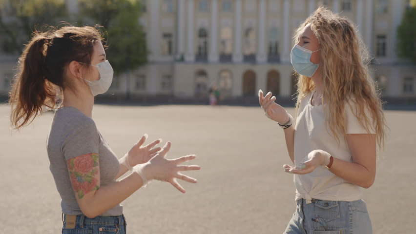 Friends in protective medical face mask greet their elbows. Social distancing. Elbow bump is new greeting to avoid spread of coronavirus or covid-19 - Avoid handshakes due to pandemic. 6K Downscale. | Shutterstock HD Video #1059248759