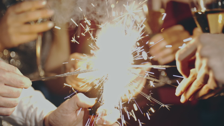 Close up portrait of friends at party celebrating birthday, drinking champagne or sparkling wine, pouring into glass, smiling, laughing, holding and waving sparkler. Happiness or fun concept.