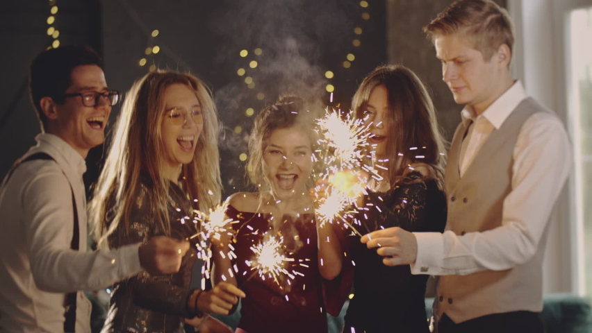 Close up portrait friends holding sparklers in hands. Guys celebrating by waving fireworks, enjoying party on New Years or Christmas Eve. Happy group of people enjoying party in evening. | Shutterstock HD Video #1059248807