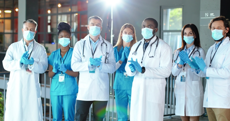 Mixed-races team of doctors applauding in hospital. International group of medics in medical masks. Protected workers. Multi ethnic physicians and nurses in uniforms in clinic. Applause. Celebrating. Royalty-Free Stock Footage #1059250154