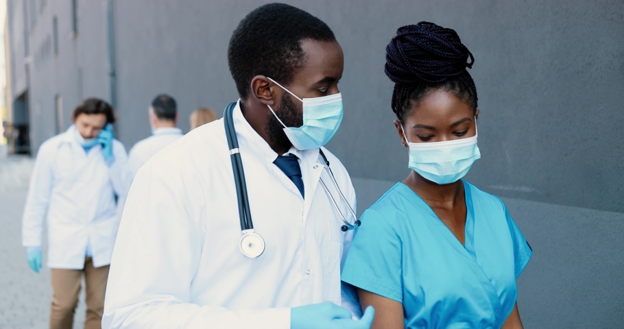 African American couple, man and woman, doctors colleagues in medical masks walking, talking and using tablet device. Male and female physicians tapping and scrolling on gadget computer. Coworking. Royalty-Free Stock Footage #1059250226