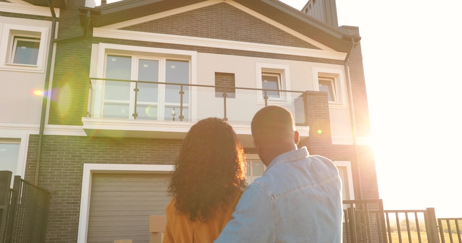 Rear on African American young just-married couple standing at yard of house, hugging and observing second floor. Back view on man and woman in hugs moving in new home. Royalty-Free Stock Footage #1059250358