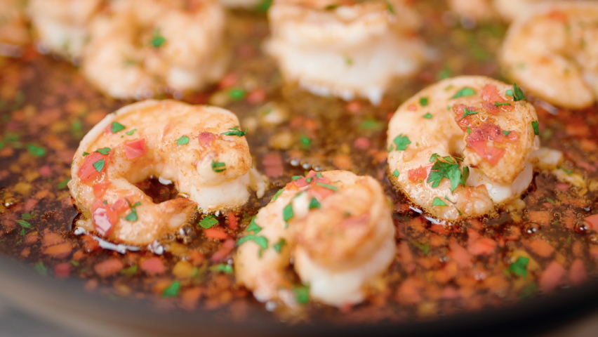 Frying shrimps/prawns in a pan with butter, oil, greens, and spices in 4K. Concept of cooking shrimps in a pan on a gas stove in slow motion. Royalty-Free Stock Footage #1059252248