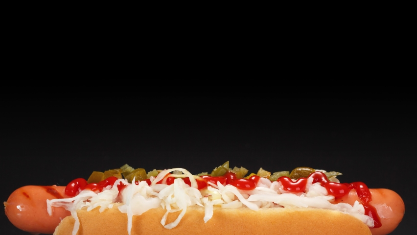 Hot dog with cream cheese, sauerkraut, jalapeno peppers and tomato sauce on a black background. | Shutterstock HD Video #1059252353