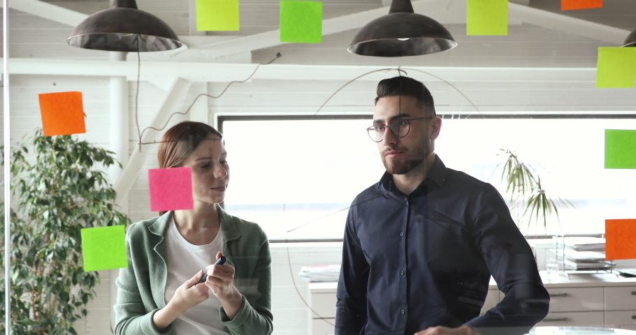 Skilled young arabian male manager drawing charts on glass agile scrum wall, explaining marketing strategy to motivated female colleague at brainstorming meeting in modern office, company lifestyle.