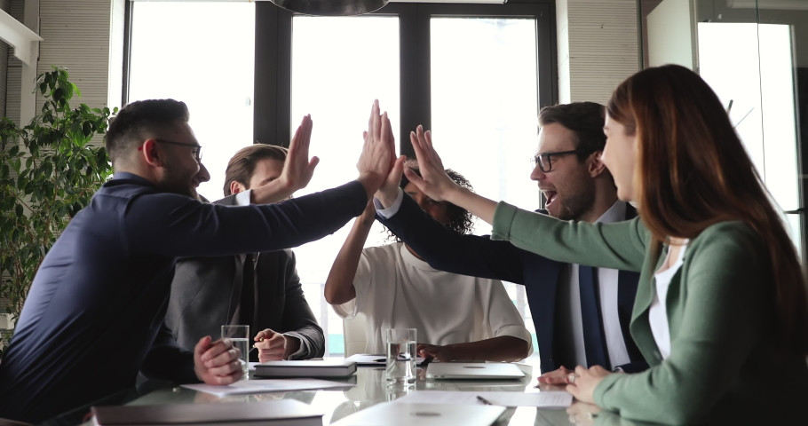 Happy young african american female team leader listening to excited male colleague in formal wear at group meeting, joining hands give high five in air celebrating corporate unity success at office.