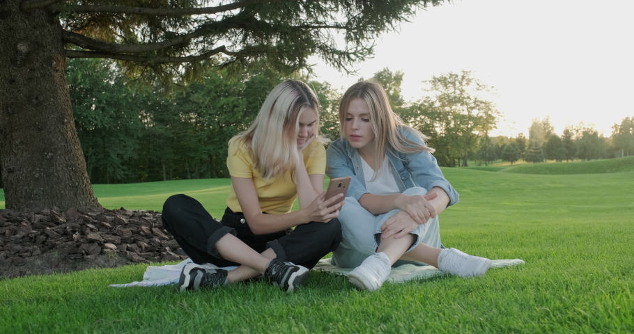 Two girlfriends sitting on green grass of lawn smiling talking looking together at smartphone screen. Youth, friendship, technology, lifestyle concept. High quality 4k footage | Shutterstock HD Video #1059252878