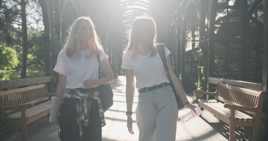 Two happy smiling talking girls teenagers students walking together, young women with backpacks, sunny day in the park background. High quality 4k footage | Shutterstock HD Video #1059252881