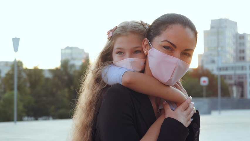 Woman in medical mask, mother holds child in hands on back on street walk in coronavirus epidemic, look lovingly at camera, supports protects baby. Mom hugs daughter in pandemic respiratory virus risk Royalty-Free Stock Footage #1059254288