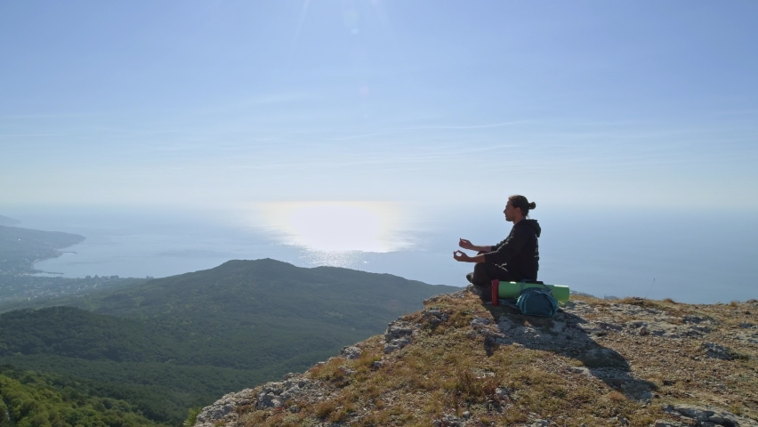 A young tourist is enjoying the sea view from a high mountain. A man drinks tea from a thermos while sitting on a cliff in the mountains in the rays of the rising sun   Shutterstock HD Video #1059254528