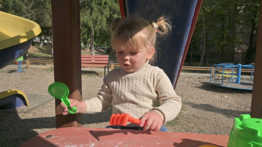 Little blond girl weirdly playing with rake and sieve on table at playground | Shutterstock HD Video #1059254987