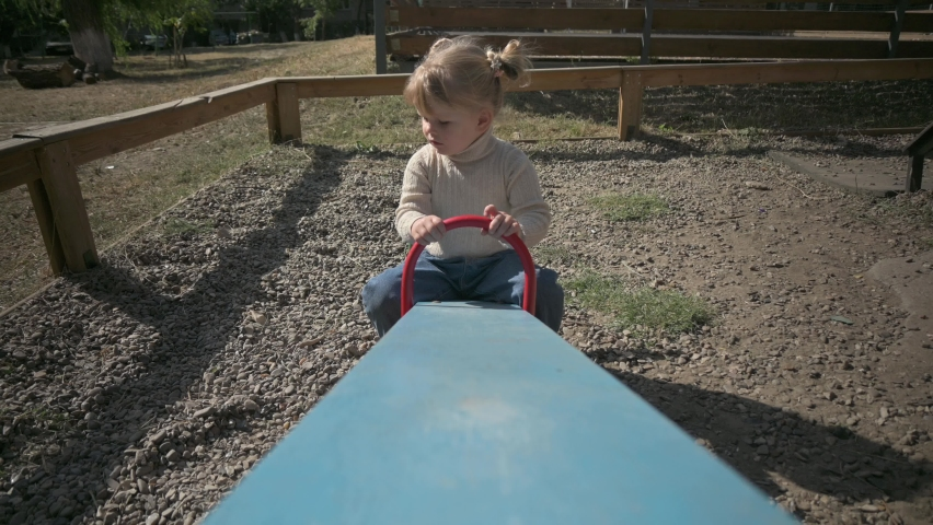 Little beautiful blond girl have fun riding the teeter totter at playground | Shutterstock HD Video #1059254990