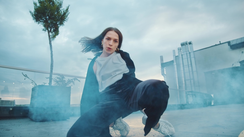 Cool aggressive young talented hip-hop woman dancing on the roof floor staring at camera performing amazing provocative gestures and movements under smoke. Artist performance. Street dance.