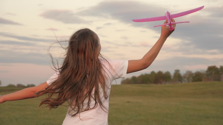 Teenager dreams of becoming pilot and astronaut. girl wants to become pilot and astronaut. Slow motion. Happy girl runs with a toy airplane on field in sunset light. children play toy airplane. | Shutterstock HD Video #1059255539