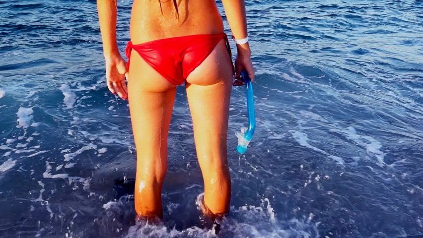 Beach vacation of girl into sea foam wave . Body part of female legs and buttock wearing red bikini holding snorkeling tube.Try go in water. Back view. Slow motion   Shutterstock HD Video #1059255773