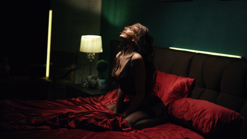 Behind door view of sexy woman throwing long curly hair back in slow motion on red silk bed. Seductive girl flirting on satin sheet in dark bedroom. Erotic model girl in lace lingerie posing on bed