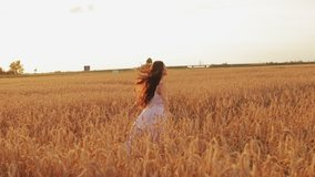 Beautiful young woman enjoys life walking on a wheat field at sunset in summer