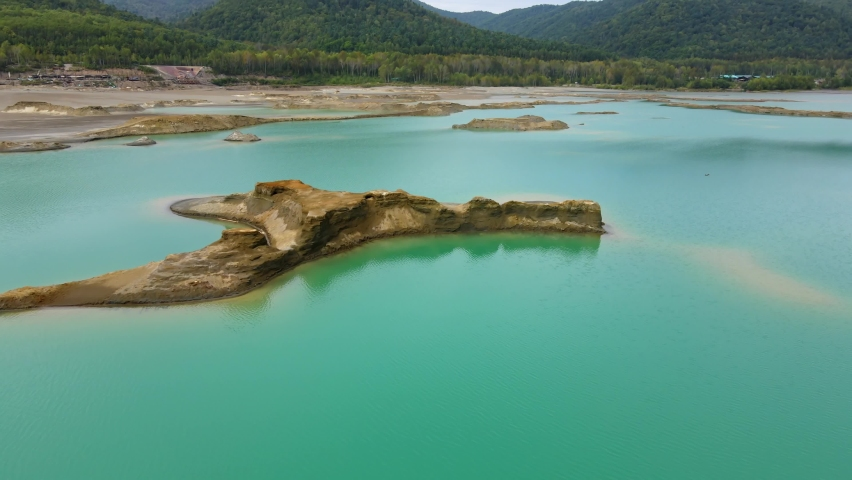 A chemical lake with turquoise water. View from above. Fly over an island in the middle of a tailing dump with toxic water from the Khrustalnensky mining and processing plant in Kavalerovo   Shutterstock HD Video #1059256235