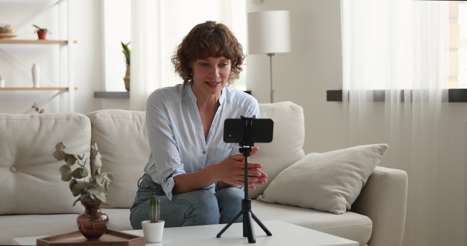 Middle-aged woman record videovlog using smart phone seated on couch alone in living room, put device on tripod film new vlog make on-line live stream, share experience, lead webinar event concept