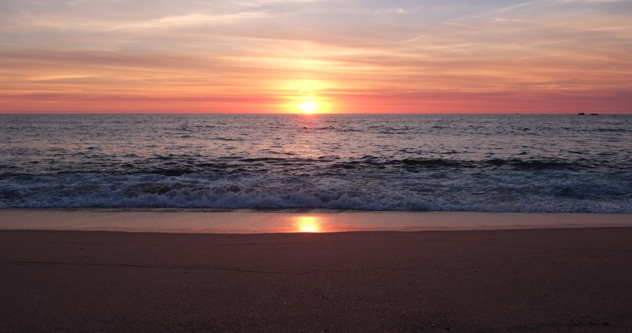 Sunset on beach in summer, with sun reflected on the wet sand. Straight shot parallel to shoreline. | Shutterstock HD Video #1059256526